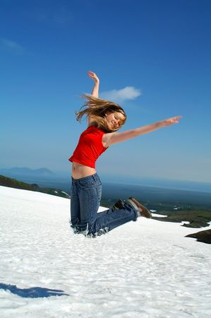 Glad girl jumps in air on background of the mountains Stock Photo