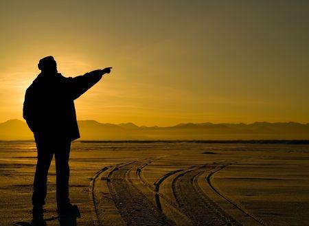 onward: A silhouetted hombre delante del sol se extiende la mano en adelante, lo que indica la direcci�n.