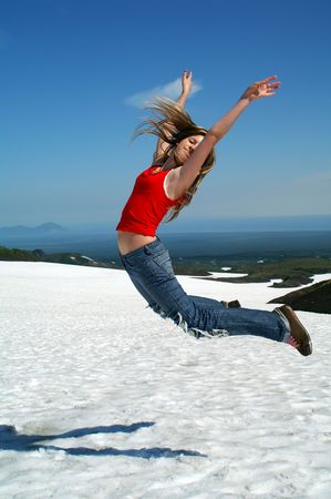 Glad girl jumps in air on background of the mountains.