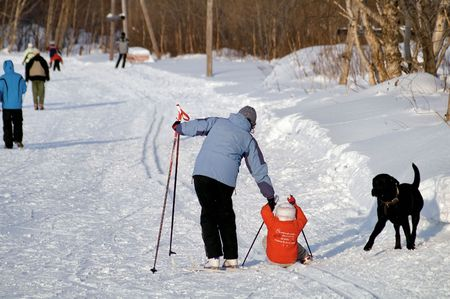 Child accidentally fell  on ski. Mother helped. photo