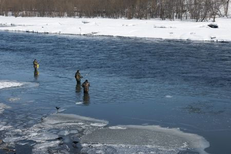 Fishermen go fishing on river during high water by springtime. photo