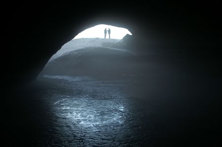 inwardly: silhouettes two talking mans beside entry in cave