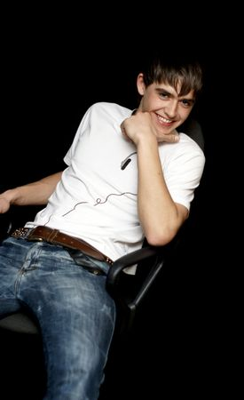 Young male model sitting on the chair and smiles