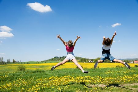 happy girls jump in field under blue sky and clouds