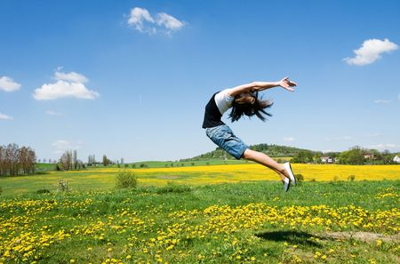 happy girl jump in field under blue sky and clouds
