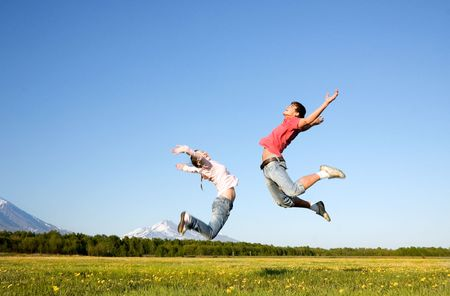 Young man and woman jumping over green field