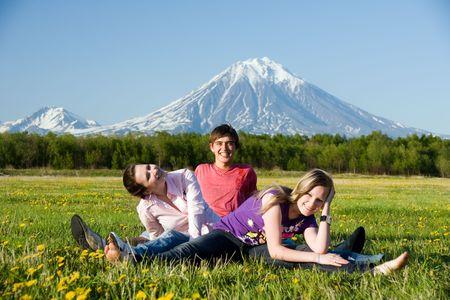 three teenager merrily repose on flowering field