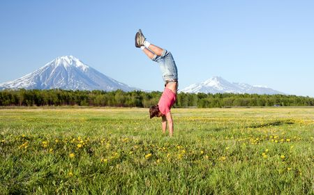 guy stands on hands in field photo