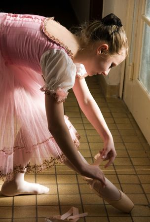young ballerina puts on pointe  before appearance