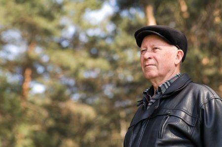 portrait of a senior person reposing in park photo