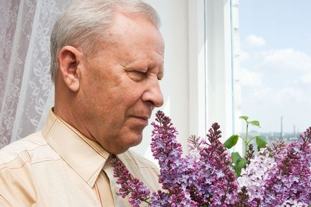 portrait of a senior person with bouquet of the lilac photo