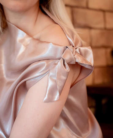 Delicate light pink silk blouse is tied with a bow on the shoulder of a beautiful young girl. The material is whitish, flowing. the photo shows the chin, neck and shoulder of the model. Close-up photo