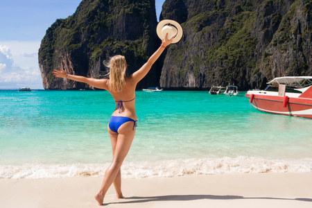 Stunning fit girl posing in turquoise sea water and enjoying sun during summer holidays on the Phi Phi islands in Thailand. Maya bay.