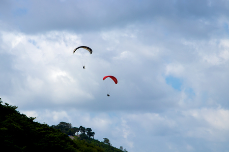 Flying two paragliders over the mountain with views of the horizon.