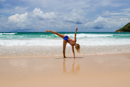 Young healthy yoga woman practicing yoga on the tropical beach. Stock Photo