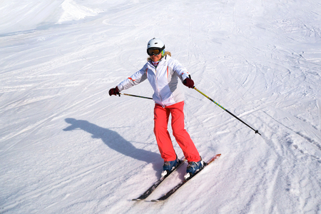 Middle aged woman alpine skiing in the snow in winter.