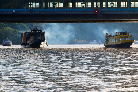 Many ships sail under the subway bridge and smoke around.