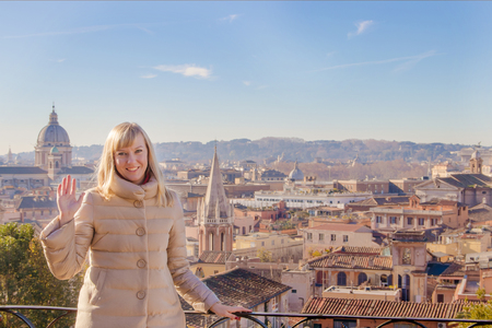 Portrait of a happy young blond woman waving her hand against the background of Rome Italy. Stock Photo