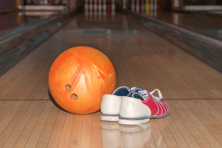 Bowling equipment close up of bowling shoes and orange ball lying on bowling alley.