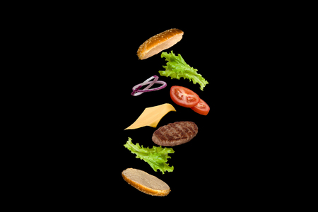 Delicious burger with flying ingredients isolated on black background. 스톡 콘텐츠