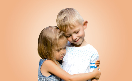 Two cute funny kids standing together and hugging. Innocent children's love. Isolated vanilla background. Stock fotó