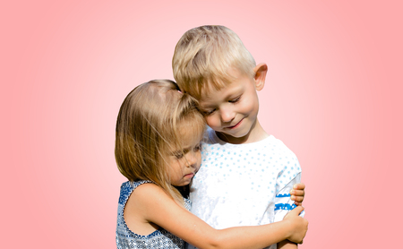 Two cute funny kids standing together and hugging. Innocent children's love. Isolated pink background.