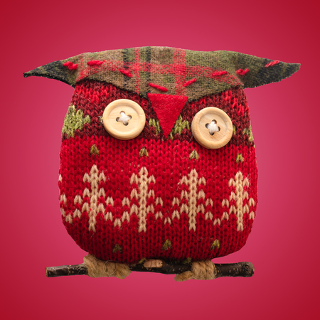 Christmas toy owl made from red and green knitted thread. Isolated red background.