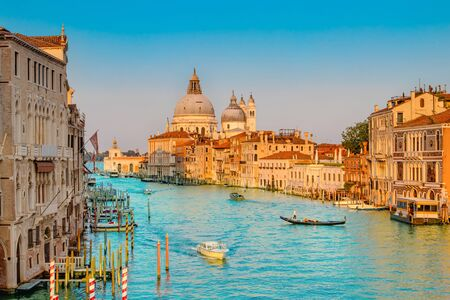 Beautiful view of traditional Gondola on famous Canal Grande with Basilica di Santa Maria della Salute in golden evening light at sunset in Venice, Italy. Imagens