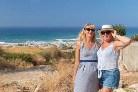 Smiling daughter and mother stand behind their backs panorama of the city beach and the sea. Stock fotó