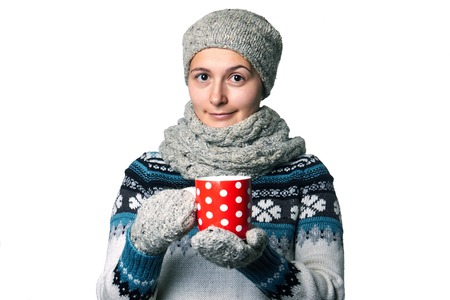 warms: beautiful young girl smiling. In a gray scarf and hat holding a red cup in his hands. warms hands