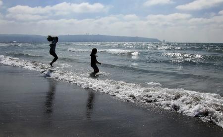 children jumping on the beach Stock Photo