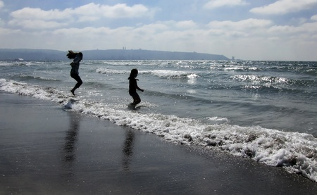 children jumping on the beach photo