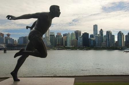 monument to man running on the background of high-rise buildings in Vancouver, Canada Imagens