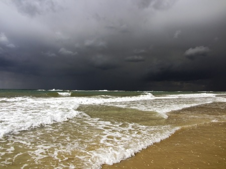 black storm clouds over the Mediterranean Sea and the waves incident on the beach