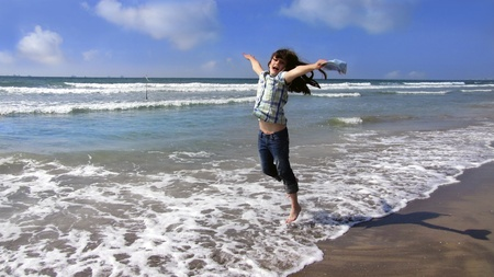 girl jumping on the waves beautiful sea and sunny weather photo