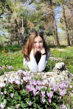 the girl in the forest among flowering cyclamens photo