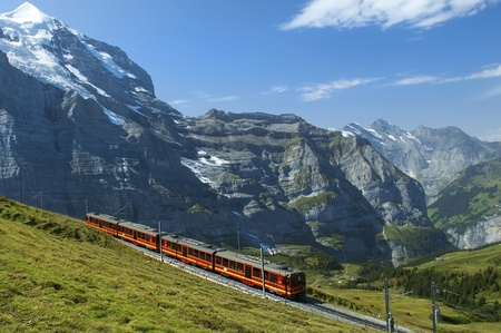 swiss alps: red train on the background of snowy peaks in the Swiss Alps Stock Photo