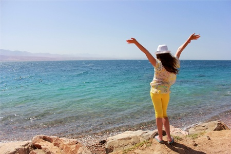 young girl in a white hat standing on the shore of the Red Sea early in the morning, raising his hands to meet the sun photo