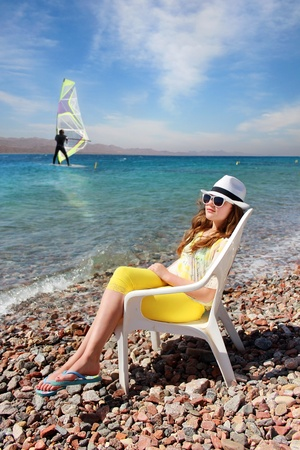 Young girl in sunglasses and a white hat resting on the sea, windsurfer in the background photo