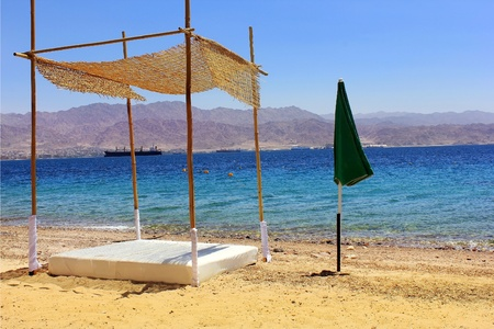 beach on the Red Sea.early in the morning without people. in the foreground of a bamboo canopy and umbrella Stock Photo - 13564912