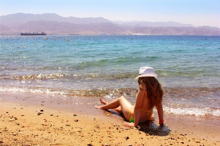 young girl with long hair in the bikini and a white hat on the beach photo