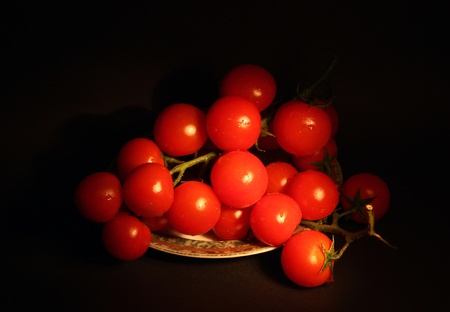 Cherry tomatoes on a branch on a black background  Photo taken in the dark with a light brush  Stock Photo