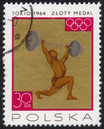 POLAND - CIRCA 1964  a stamp printed by POLAND shows the athlete raises a barbell, the inscription gold medal, series, circa 1964 Stock Photo - 13601939