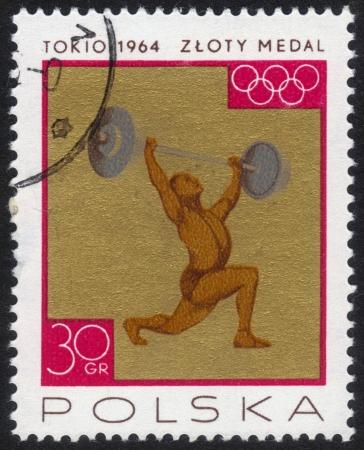 POLAND - CIRCA 1964  a stamp printed by POLAND shows the athlete raises a barbell, the inscription gold medal, series, circa 1964 Stock Photo - 13601939