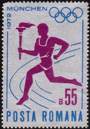 deportes olimpicos: Rumania - CIRCA 1972 un sello impreso por Rumania muestra a un corredor que lleva la antorcha con la llama olímpica, dedicada a los Juegos Olímpicos en Munich, alrededor del año 1972