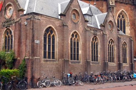 dozens: urban landscape in the Netherlands, a small church and dozens of bicycles parked near its wall