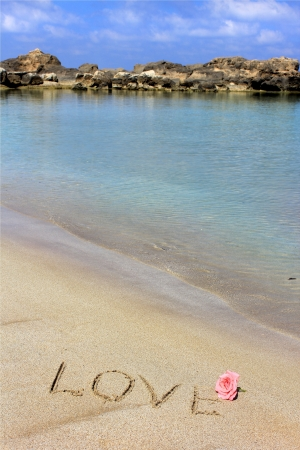 Inscription love on the wet sand of the sea, beach in a quiet cove of the Mediterranean Sea and  flower of  rose photo