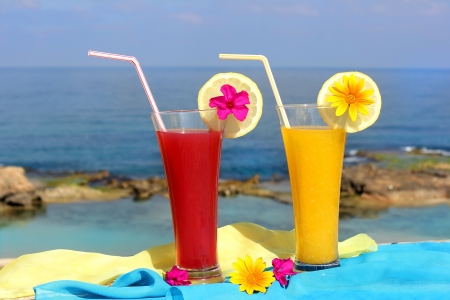 red and yellow fruit cocktails on the background of beautiful sea landscape Stock Photo - 14126146