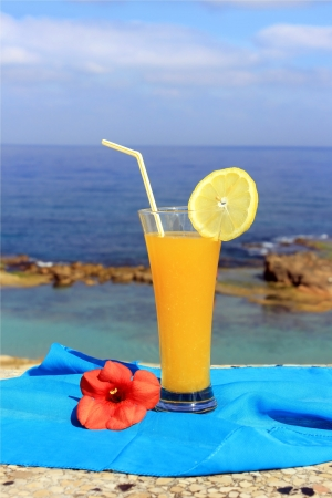 yellow fruit cocktail on the background of a beautiful sea landscape Stock Photo - 14126142