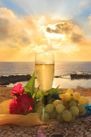 glass of white wine, grapes and flowers on a background of sea and sky at sunset Standard-Bild